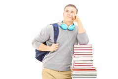 Male student with headphones deep in thoughts on a pile of books. Isolated on white background Royalty Free Stock Photo