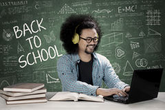 Male student hearing music on a headphone. Image of a male college student is using a laptop and hearing a music while sitting with scribbles on the chalkboard Stock Images