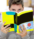Male student hiding his face behind a book. In a library Royalty Free Stock Photos