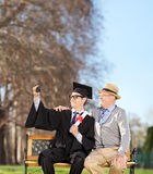 Male student and his father taking selfie in park Royalty Free Stock Photography