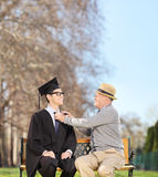Male student and his proud father sitting in park. Graduate student and his proud father sitting on a wooden bench in park shot with tilt and shift lens Stock Photo