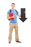 Male student holding a big black arrow Royalty Free Stock Images