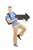 Male student holding a big black arrow Royalty Free Stock Image