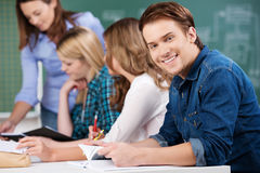 Male Student Holding Book With Classmates And Teacher At Desk. Portrait of young male student holding book while sitting with female classmates and teacher at Royalty Free Stock Photos