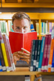 Male student holding book in front of his face in the library. Close up of a young male student holding book in front of his face amid bookshelves in the college Stock Photos