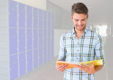 Male student holding book in front of lockers. Digital composite of male student holding book in front of lockers Royalty Free Stock Photo