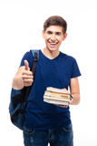 Male student holding book and showing thumb up. Happy male student holding book and showing thumb up isolated on a white background. Looking at camera Royalty Free Stock Image