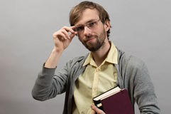 Male student holding books. Against grey wall background Stock Images