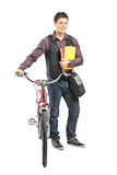 Male student holding books and pushing a bike Royalty Free Stock Images