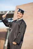 Male Student Holding Diploma On Graduation Day At. Portrait of confident male student holding diploma on graduation day at college campus Stock Photos