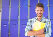 Male student holding files in front of lockers Royalty Free Stock Image