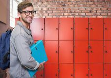 Male student holding folder in front of lockers Royalty Free Stock Images