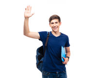 Male student holding folder and showing greeting gesture. Happy male student holding folder and showing greeting gesture isolated on a white background. Looking Stock Photos