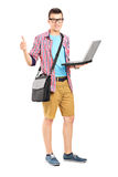 Male student holding a laptop and giving thumb up. Full length portrait of a male student with a shoulder bag, with a laptop giving thumb up  on white background Stock Photo
