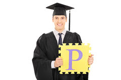 Male student holding a piece of puzzle. With the letter p on it isolated on white background Royalty Free Stock Image