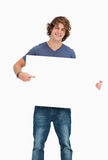 Male student holding and pointing a white board. Male student posing while holding and pointing a white board Stock Photo
