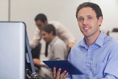Male student holding a tablet sitting in front of computer. In computer class Royalty Free Stock Photo