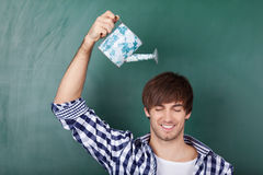 Male Student Holding Watering Can. Portrait of handsome young male student holding watering can representing growth of ideas Royalty Free Stock Photo