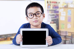 Male student holds blank tablet screen. Portrait of cute little boy sitting in the class while wearing glasses and showing a digital tablet with empty screen Stock Photos