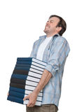 Male student holds heavy stack of books Stock Photos