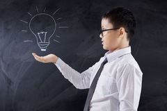 Male student holds light bulb icon. Photo of a male elementary school student holding a light bulb icon on the chalkboard Royalty Free Stock Image
