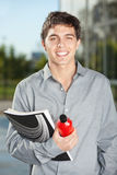 Male Student With Juice Bottle And Book Standing. Portrait of happy male student with juice bottle and book standing on university campus Royalty Free Stock Images