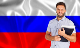 Male student of languages on Russian flag.  stock image