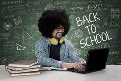Male student with laptop in the classroom. Picture of a male college student is typing on a laptop and sitting in the classroom with scribbles on the chalkboard Stock Photos