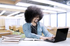 Male student with a laptop and earphone. Image of a male college student is studying with a laptop and books on the desk while using an earphone in the classroom Stock Photography