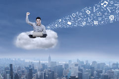 Male student with a laptop over cityscape. Asian male student working with his laptop sitting on a cloud over cityscape Royalty Free Stock Photo