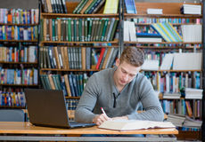 Male student with laptop studying in the university library.  Royalty Free Stock Photography