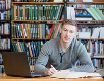 Male student with laptop studying in the university library Stock Image