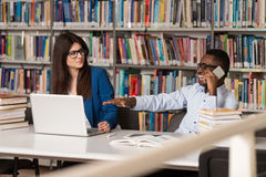Male Student Laughing AT College. Handsome Two College Students With Laptop And Books Working In A High School - University Library - Shallow Depth Of Field Stock Image