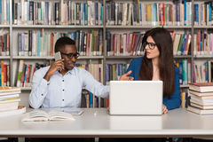 Male Student Laughing AT College. Handsome Two College Students With Laptop And Books Working In A High School - University Library - Shallow Depth Of Field Royalty Free Stock Photo