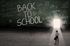Male student leading to the door school. Back to school: Text of back to school on the blackboard with a door on the board Royalty Free Stock Images