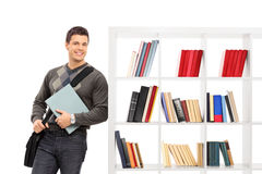Male student leaning on a bookshelf. Isolated on white background Royalty Free Stock Image