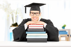 Male student leaning on a stack of books indoors Royalty Free Stock Photo