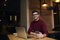 Male student learning using modern technology for preparing homework task. Portrait of cheerful handsome professional content manager of website chatting in Royalty Free Stock Image