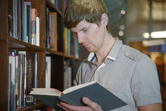 Male student in a library. Handsome european male student standing by a bookshelf in a library and reading a book Stock Photography