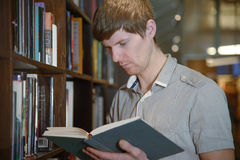 Male student in a library. Handsome european male student standing by a bookshelf in a library and reading a book Royalty Free Stock Image