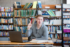 Male student in a library showing finger up.  Royalty Free Stock Photos