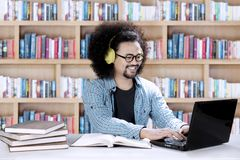 Male student listening music in the library. Picture of a male college student listening music with a headphone while studying in the library Royalty Free Stock Photos