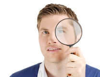 Male student looking through a magnifying glass Stock Photos