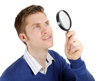 Male student looking through a magnifying glass Royalty Free Stock Photo
