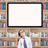 Male student looking up at whiteboard. Cute little student standing in the library under empty board while thinking ideas Stock Photos