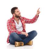 Male student in lumberjack shirt sitting and pointing up Stock Image