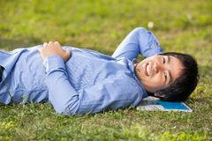Male Student Lying On Grass At College Campus. Portrait of relaxed male student lying on grass at college campus Royalty Free Stock Photos