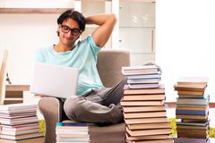 The male student with many books at home stock photography