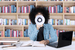 Male student with a megaphone in the library. Male college student shouting by using a megaphone while studying with a laptop and textbooks in the library Royalty Free Stock Image