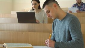 Male student notes from the book. Attarctive male student noting from the book. Handsome caucasian guy sitting on the bench at the desk. Brunette undergraduate Stock Photography
